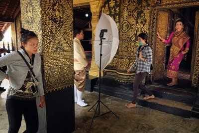 Bride and groom taking photos at a temple, Luang Prabang