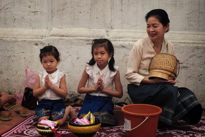 Mother with daughters preparing to give alms to the monks, Luang Prabang