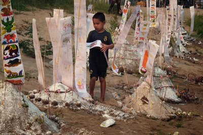 Boy draping flags on a sand stupa, Luang Prabang