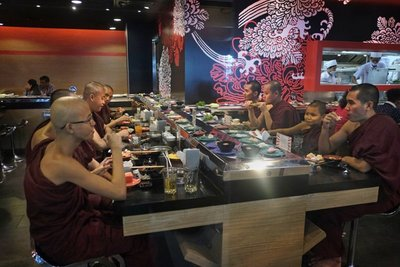 Young monks eating sushi in a trendy restaurant, Yangon