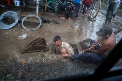 A young man cleans a drain after heavy rains, Yangon