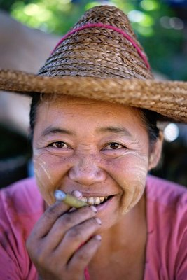 Woman smoking a freshly-rolled cigar, Thantaung village market, Lake Inle
