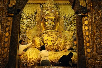 Men placing gold leaf on a Buddha at the Mahamuni Temple, Mandalay