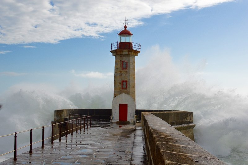 Waves crash into Porto's lighthouse.