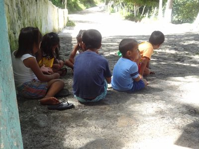 A group of the younger kids sitting around waiting to go swimming.