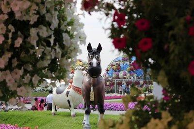 Horse peeping through a bush of flowers