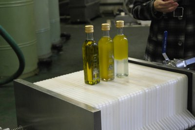 The olive oil before it goes into the distillers, before it is filtered and after filtration