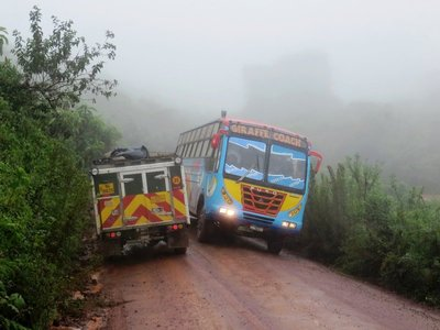 Vehicles in the rain on the road around the Ngorongoro Crater