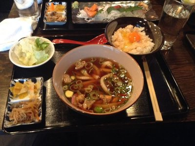 Kasu udon with raw egg on top of white rice.