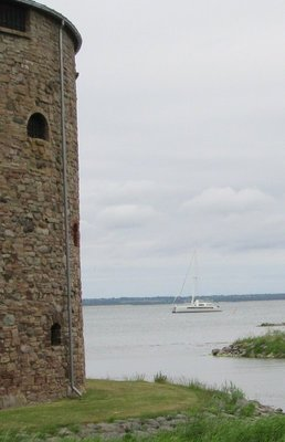 Castle sits on the shore, boat at anchor nearby