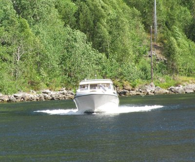 Boat coming out of strait between lake and fjord