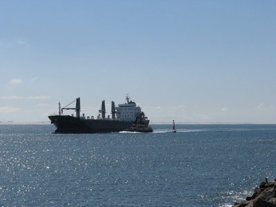 Ocean freighter coming into port for coal with pilot boat