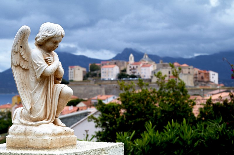 Angel Statue with Calvi Old Town in Background