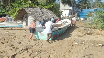 Helping shift fishing boats from the eroding beach front