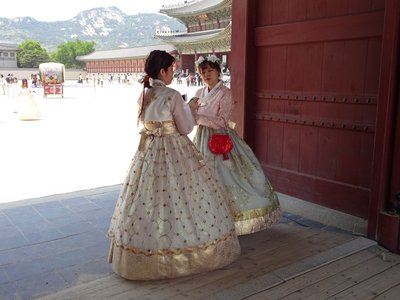 Girls in hanbok checking their smartphones, Gyeongbokgung Palace