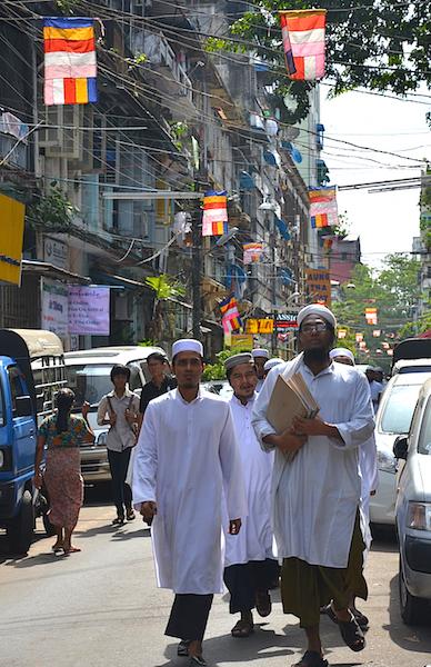 Muslim men walking under Buddhist flags