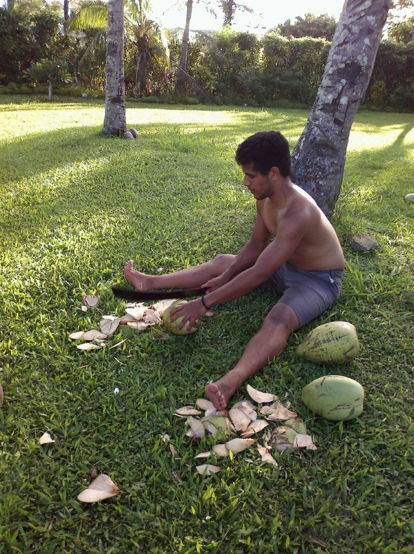 A man is opening a coconut in Tonga