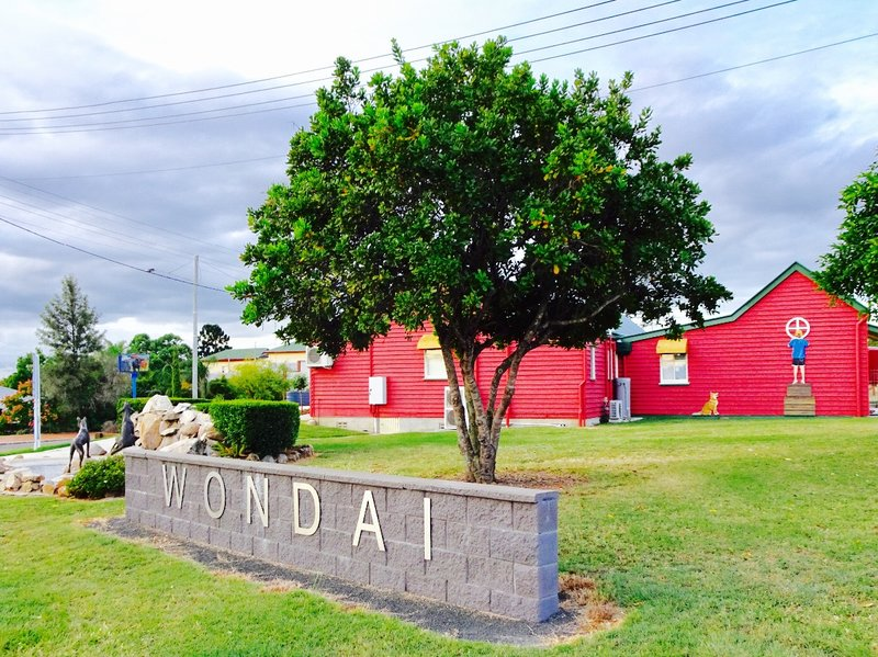 This brightly colored building is the Wondai Shire Regional Art Gallery. It is in the former Staion Master's home.  Appropriately, there is a dingo sculpture here!.