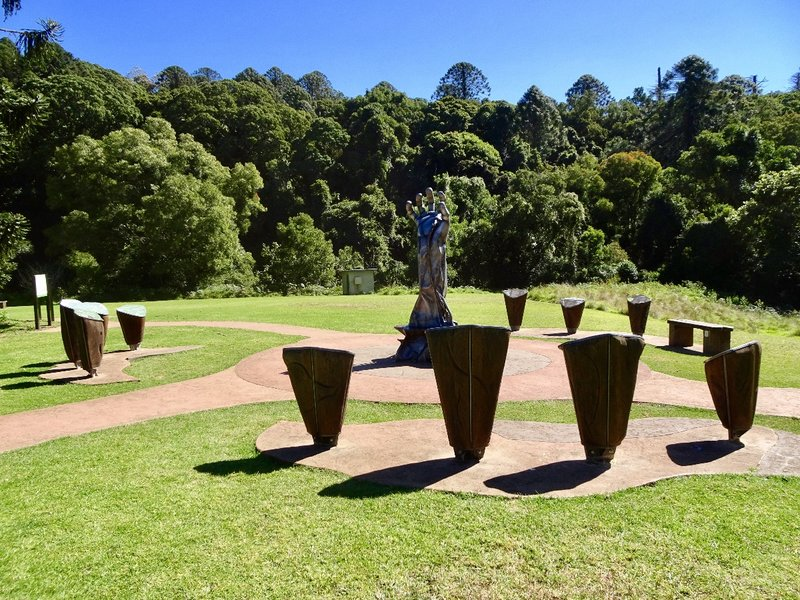 The kernels of the Bunya pine cone are on display here; on top of each kernel is a story about the Aboriginal connection to this area. In the background, the tall conical trees are Bunya pines.