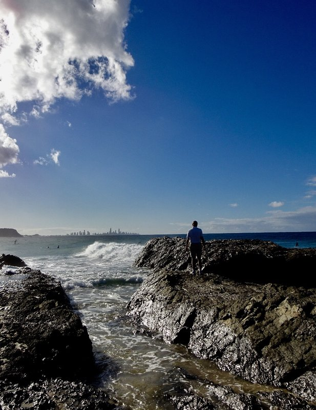 Greg is standing on the Currumbin Rocks, and he is looking at the tall skyline of Surfer's Paradise.