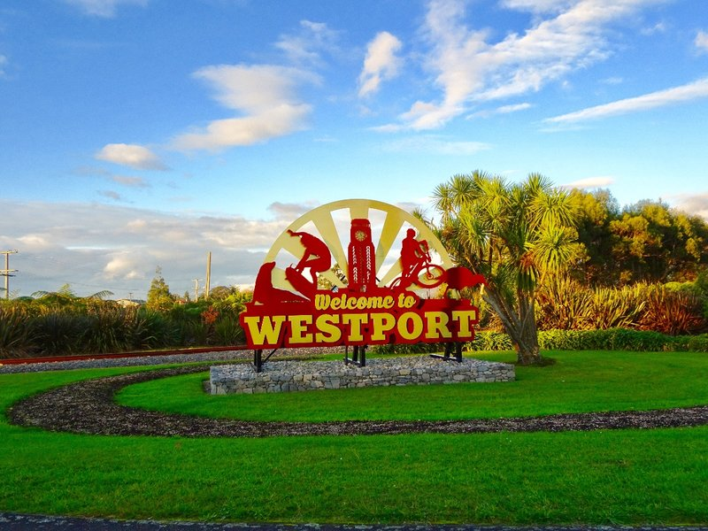 The Westport sign with a cabbage tree on it's right. This palm is a native tree and can be seen all over NZ.