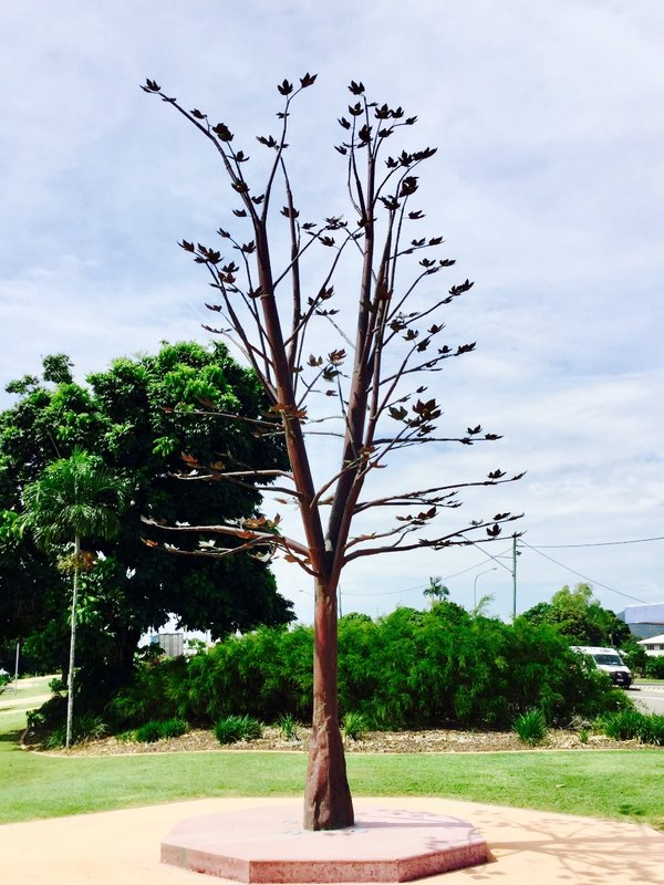"""A symbol of reconciliation, this flame tree sculpture was designed to stand over 8m high, with water flowing from points along the branches during the day and gas fueled flames that lit up the tree at night.""  As Cyclone Yasi devastated Cardwell in 2011, the copper flame tree was bent over at a severe angle, but it did not break. It was restored, and is now also a symbol of the communities ability to bounce back from this disaster. The flame tree is a common rainforest tree in this area."