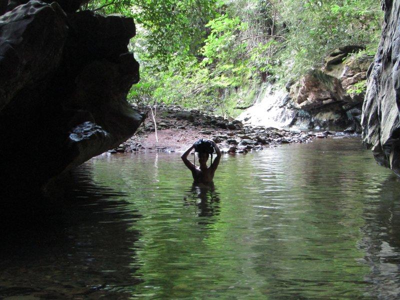 Loic crossing the river in Deer Cave