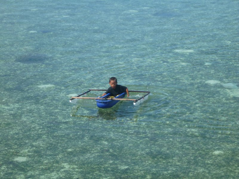 A boy paddling a homemade boat with his flip flops
