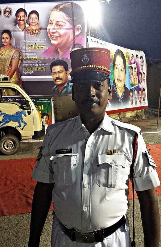 Policeman in képi with poster of Jayalalitha behind him on poster