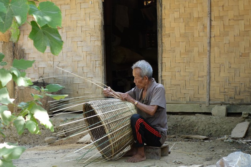 A grandfather braiding a basket