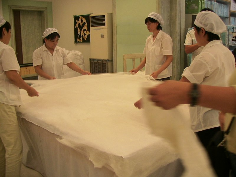 Stretching the silk to make a silk blanket