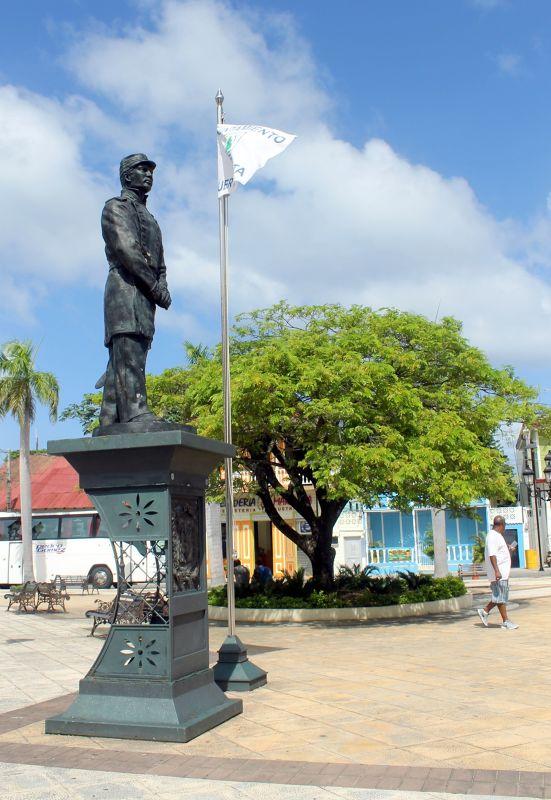 Statue of General Gregorio Luperón with blue building in back - Puerto Plata