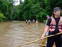 Down the river on bamboo rafts... Oh that is Jim, an American with a killer mullet