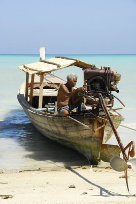 Moken man is repairing his boat by the beach,Koh Surin,PhangNga.Thailand