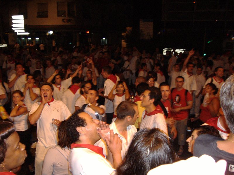 Red and white clad people sign along with traditional basque music.