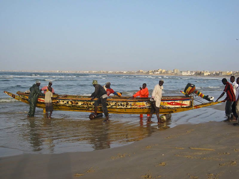 Launching the pirogue (fishing boat) into the ocean