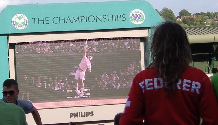 A fan watches Federer on the big screen, Wimbledon