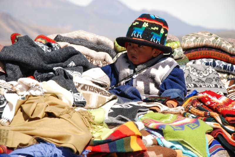 A young boy hiding on his mother's clothes stall