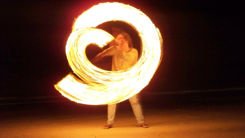 Solo fire dancer practicing on the beach