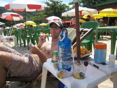 Dave enjoying some munchies at Praia do Meio in Trinidade, just south of Paraty. Brazilian beaches are lined with plastic chairs and tables. Just buy a drink and the table is yours for the day! It is rare to see people sitting in their own chairs or on beach towels.