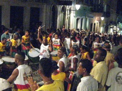 Another percussion band marching through the street, gathering a big following of dancing people.