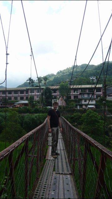 Adam walking over rickety Banaue Bridge