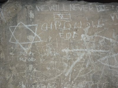 Visitors writing on barrack wall camp II