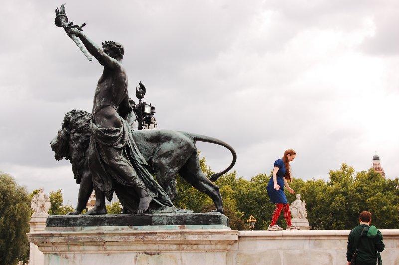 Tourists climbing outside Buckingham Palace