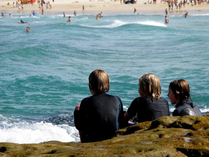 3 chavalines oteando el panorama a la espera de buenas olas para surfear en North Bondi, Sydney.