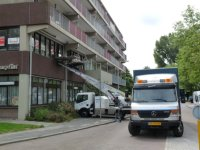 Moving house, dutch style, using a conveyor to lift household contents in and out of an upstairs window