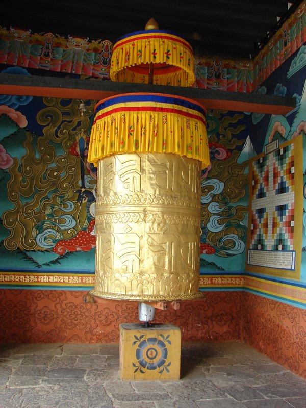 Giant prayer wheel beside door to Punakha Dzong