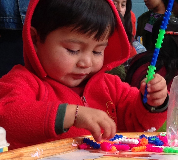 One of the children playing at the group table