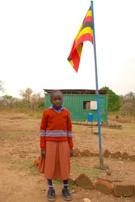 A little girl poses beneath the Ugandan flag at school