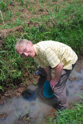 Dad collects stream water to water REAP plants